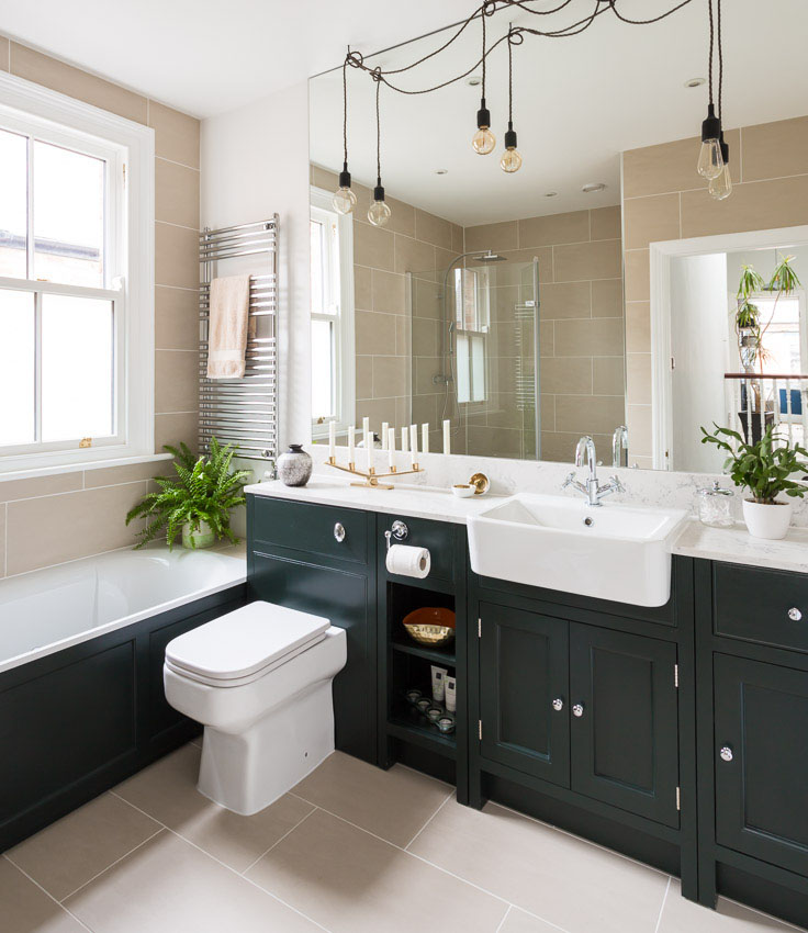 styled dressed bathroom with full heaight mirror, beige tiles, obsidian green little greene inframe units and bare bulb pendant lights
